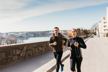 Couple running on street in Stockholm, Swedenの写真素材 [FYI02210996]