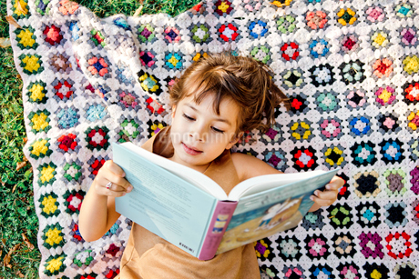 Girl reading on picnic blanket in Friseboda, Swedenの写真素材 [FYI02211003]