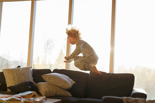Boy jumping on sofaの写真素材 [FYI02211005]