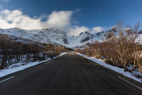 A snowy rural road with a mountain view in Norwayの写真素材 [FYI02211019]
