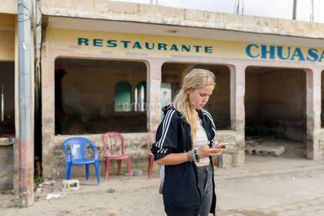Woman texting outside of restaurant in Atitlan, Guatemalaの写真素材 [FYI02211038]