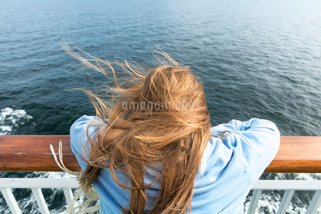 Sweden, Sodermanland, Rear view of blonde girl (10-11) leaning on railing on cruise shipの写真素材 [FYI02211042]