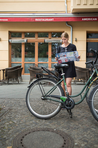 Germany, Berlin, Young woman with city map and city bicycleの写真素材 [FYI02211043]