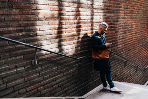 Man beside brick wall on smart phone in Swedenの写真素材 [FYI02211082]