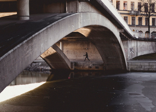Person walking under bridge during winter in Stockholm, Swedenの写真素材 [FYI02211083]