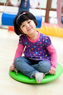 Cute girl sitting on a big toy dreidel in kindergartenの写真素材 [FYI02211087]