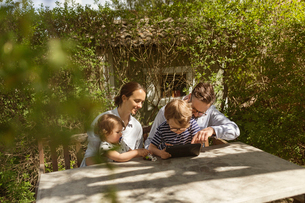 Family sit at an outdoor table using a device in Swedenの写真素材 [FYI02211113]