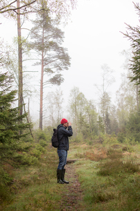 Mid adult man in a misty forest in Lerum, Swedenの写真素材 [FYI02211114]