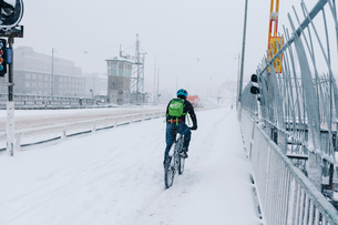 Man cycling in snow in Stockholmの写真素材 [FYI02211117]
