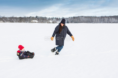 Mother playing with child in snow in Swedenの写真素材 [FYI02211124]