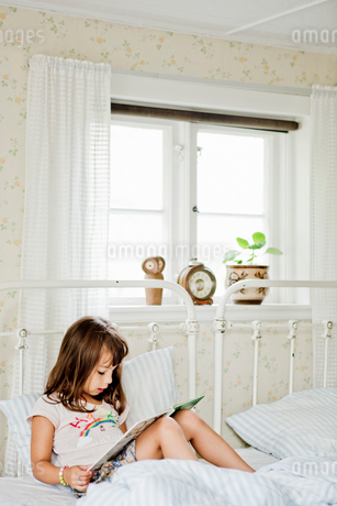 Girl reading in bedの写真素材 [FYI02211144]