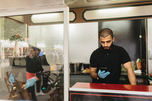 Food truck worker checking his cell phoneの写真素材 [FYI02211178]