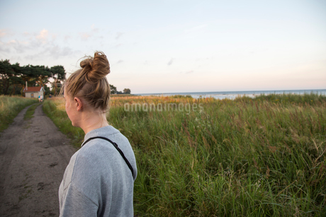 Young woman standing on an unpaved road in Ornahusen, Swedenの写真素材 [FYI02211187]