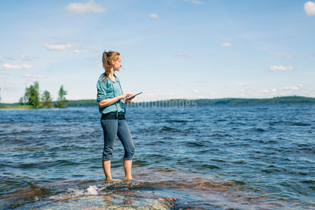 Mid adult woman holding a tablet standing in a lake in Finlandの写真素材 [FYI02211192]