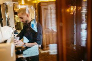 Man making coffee in bakery in Swedenの写真素材 [FYI02211211]