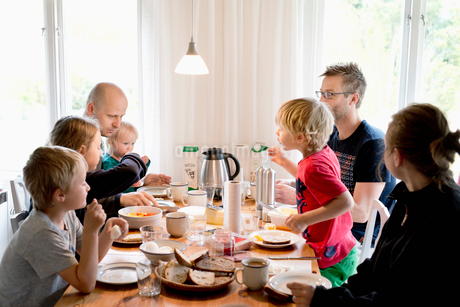 Sweden, Family with children (2-3, 4-5,10-11,16-17) eating breakfast at tableの写真素材 [FYI02211260]