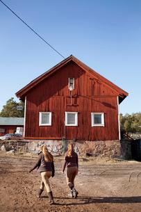 Sweden, Uppland, Faringso, Young female horse riders walking through farmの写真素材 [FYI02211272]