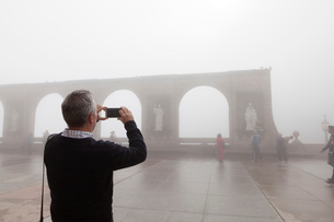 Man taking a photograph in mist in Barcelonaの写真素材 [FYI02211286]