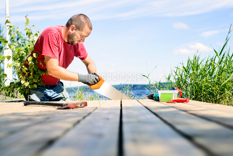 Mid adult man sawing a deck in Finlandの写真素材 [FYI02211289]