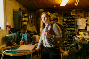 Teenage girl holding coil of rope in rope maker shopの写真素材 [FYI02211300]