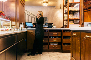 Woman on phone at bakery counter in Swedenの写真素材 [FYI02211315]