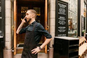 Baker on phone outside bakery in Swedenの写真素材 [FYI02211349]