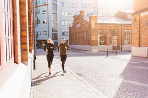 Man and woman running along street in Stockholm, Swedenの写真素材 [FYI02211350]