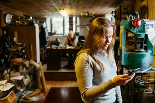 Teenage girl looking at her phone in rope maker shopの写真素材 [FYI02211357]