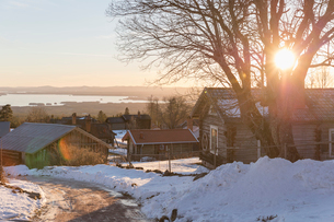 Sunrise over houses in Dalarna, Sweden during winterの写真素材 [FYI02211367]