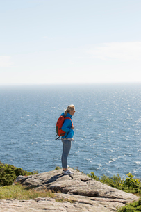 Mid adult woman standing on a cliff over the sea in Kullberg, Swedenの写真素材 [FYI02211372]