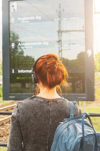 Woman wearing headphones by train signの写真素材 [FYI02211379]
