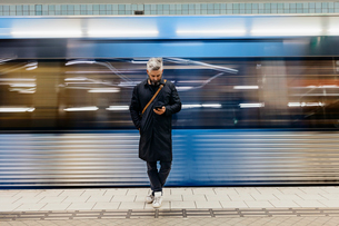 Man texting at train station in Stockholm, Swedenの写真素材 [FYI02211389]