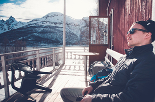 Man sitting on balcony with snowcapped mountains in background in Troms Fylke, Norwayの写真素材 [FYI02211422]