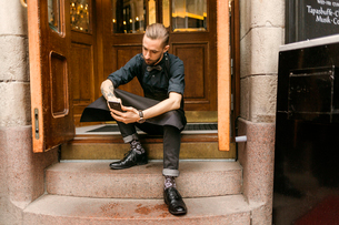 Baker on steps outside bakery in Swedenの写真素材 [FYI02211427]