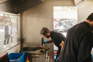 Chef cooking burgers on the grill in a food truckの写真素材 [FYI02211456]