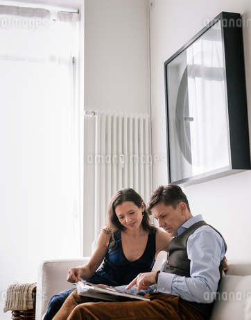 Germany, Couple sitting on sofa an reading bookの写真素材 [FYI02211479]