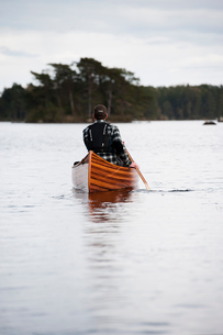 Sweden, Smaland, Mature man in boat on lake with forest on horizonの写真素材 [FYI02211485]