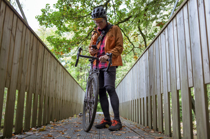 Mid adult man with a bicycle on a bridge in Harskogen, Swedenの写真素材 [FYI02211525]