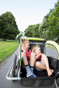 Sisters in bicycle trailer in Smaland, Swedenの写真素材 [FYI02211526]
