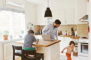 Mid adult man and children in a domestic kitchen in Swedenの写真素材 [FYI02211554]