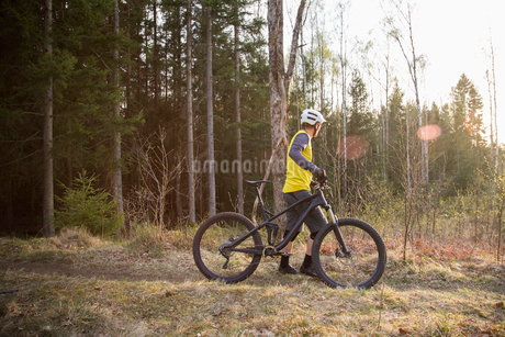 Mid adult man with a mountain bike in a forestの写真素材 [FYI02211607]