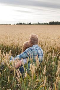 Finland, Uusimaa, Siuntio, Mid adult couple sitting in wheat fieldの写真素材 [FYI02211619]