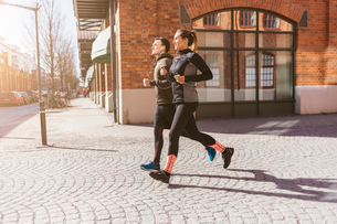 Man and woman running along street in Stockholm, Swedenの写真素材 [FYI02211650]