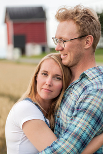Finland, Uusimaa, Siuntio, Mid adult couple embracing in fieldの写真素材 [FYI02211658]