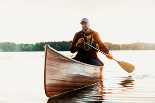 Sweden, Smaland, Mature man in boat on lake surrounded by forestの写真素材 [FYI02211666]