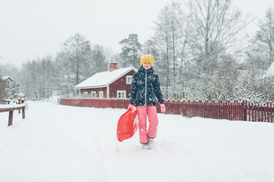 Girl holding a sled on snowの写真素材 [FYI02211682]
