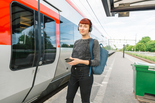 Woman wearing headphones on train platformの写真素材 [FYI02211688]