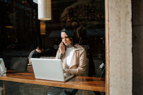 Woman on the phone by a laptopの写真素材 [FYI02211703]