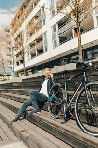 Man on staircase with bicycle in Sodermanland, Swedenの写真素材 [FYI02211725]