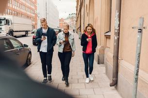Teenagers walking down a city street looking at their phones in Swedenの写真素材 [FYI02211726]